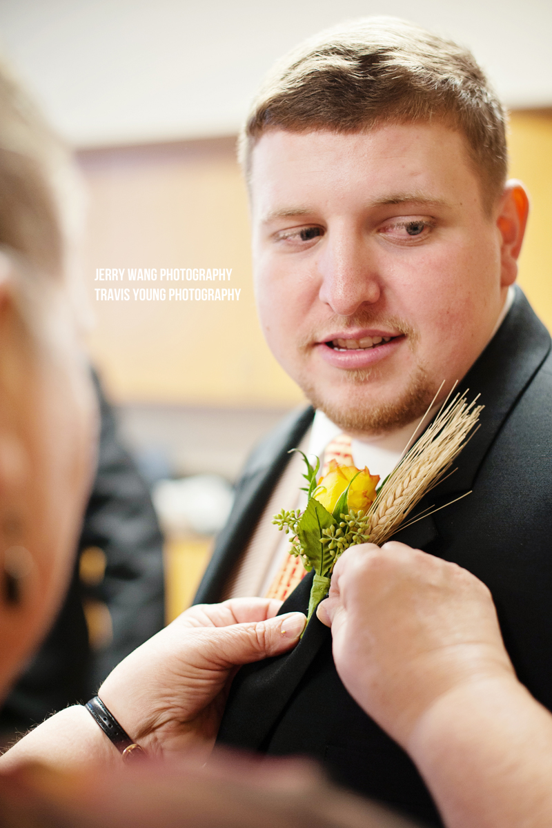 The groom getting his boutonniere pinned
