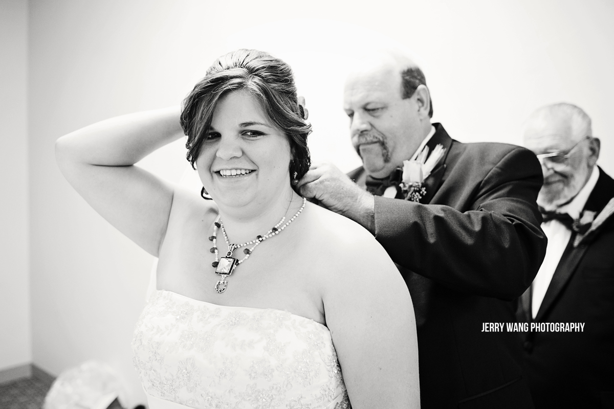 The father of the bride putting on a necklace for her.